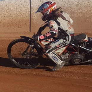 young female in full leathers on speedway bike riding on dirt track