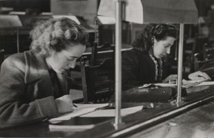 Black and white imagephoto of two women leaning over documents on a desk, pen in hand. Looks like the photo was taken in the mid 20th century.