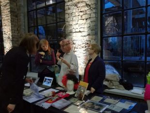 Some of the Community Curators discuss their work with a visitor, beside a table displaying items from the GWL collection including photographs, postcards, badges and a fluorescent yellow, orange and brown curly wig.