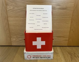 A red first aid box with a piece of paper standing in it. The paper is titled 'Distraction Technique' and has words like 'Hip Pain,' 'Multiple Sclerosis,' and 'Fibromyalgia' on it.
