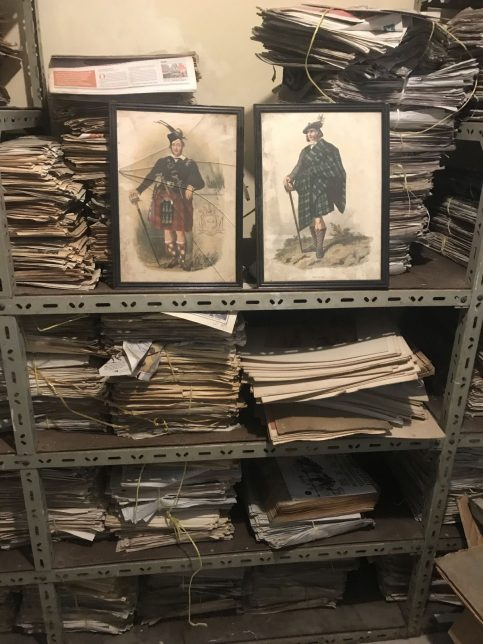 Framed prints of Scotsmen in the stores at McMillan Library. The prints, which are old-fashioned fading prints of men in kilts, are propped up on metal shelves full of papers.