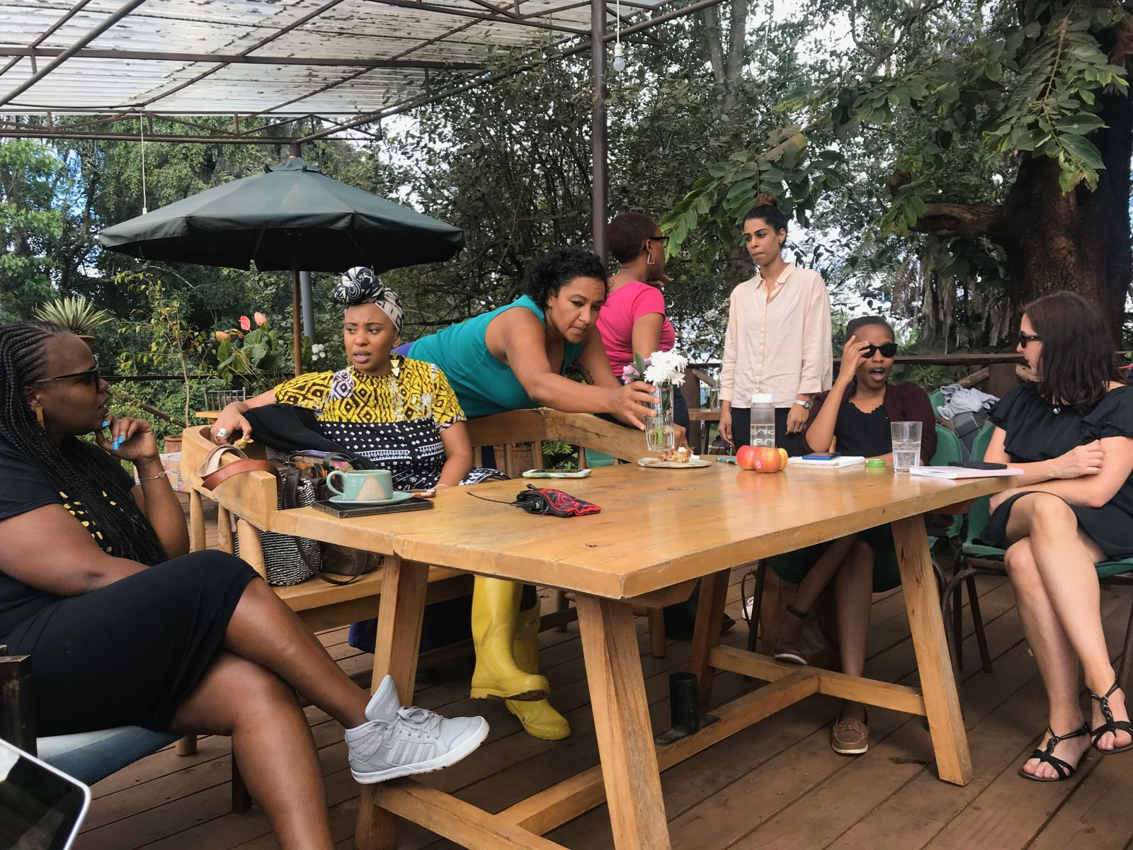 Feminist leaders assembling for gathering, Feminist Governance: A Nairobi perspective. Seven women, mostly women of colour, sit and stand talking together on a balcony with trees beyond.