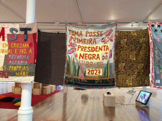 Artworks by Randolpho Lamanier, 2018. Several colourful banners hang in an high-ceilinged room. The central banner, featuring stylised plants in green, pink and blue, reads 'Toma posse primeira Presidenta Negra do Brasil 2027' ('First Black President of Brazil takes office 2027')