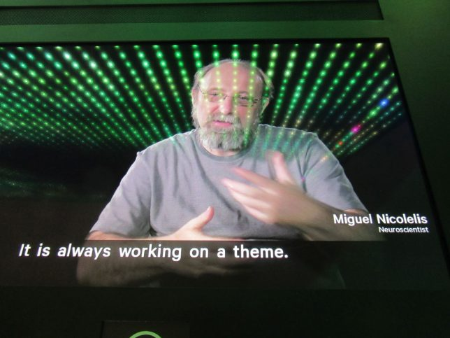 Photo of a video screen featuring a balding, grey-bearded white man gesturing as he speaks. The subtitles on the screen read 'It is always working on a theme'.