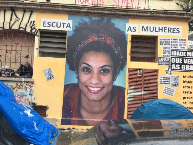 Street artwork memorialising murdered politician, feminist, lesbian activist Marielle Franco. A large photo of Marielle Franco with a vivid smile has been pasted on a wall; text aound the photo reads 'Escuta as mulheres' ('Listen to women').