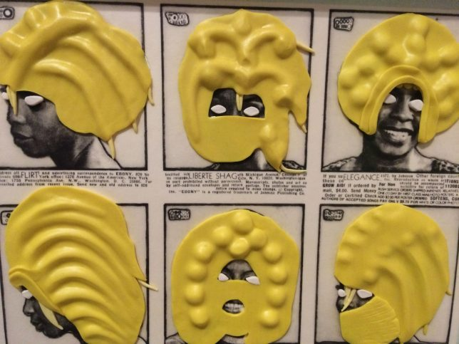 Detail of work by Ellen Gallagher, DeLuxe, 2004-5, images with plasticine. The work features black and white photos of black women taken from vintage adverts, which have then had their eyes covered in white plasticine and their hair (and sometimes faces) covered in yellow plasticine.