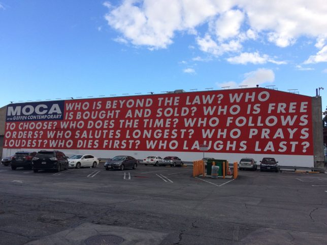 Barbara Kruger (reinstalled) wall work, Untitled (Questions) (1990/2018). On a large building, in white, bold, sans serif capitals on a red background, the 9 questions are: 'Who is beyond the law? Who is bought and sold? Who is free to choose? Who does the time? Who follows orders? Who salutes the longest? Who prays loudest? Who laughs last?'