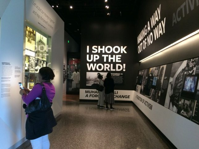 Interior of National Museum of African American History and Culture, Washington D.C., 24th March, 2019. There are photos of black activists on the walls, and a large caption in bold white capitals on a black background that reads 'I shook up the world!'