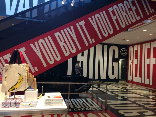 Detail of Barbara Kruger artwork Belief and Doubt, 2012, (You want it, You Buy it, You forget it) next to museum shop display. 'You want it, You Buy it, You forget it' runs in bold, white capitals on a red background up an escalator; sections of further slogans can be seen on the walls beyond.