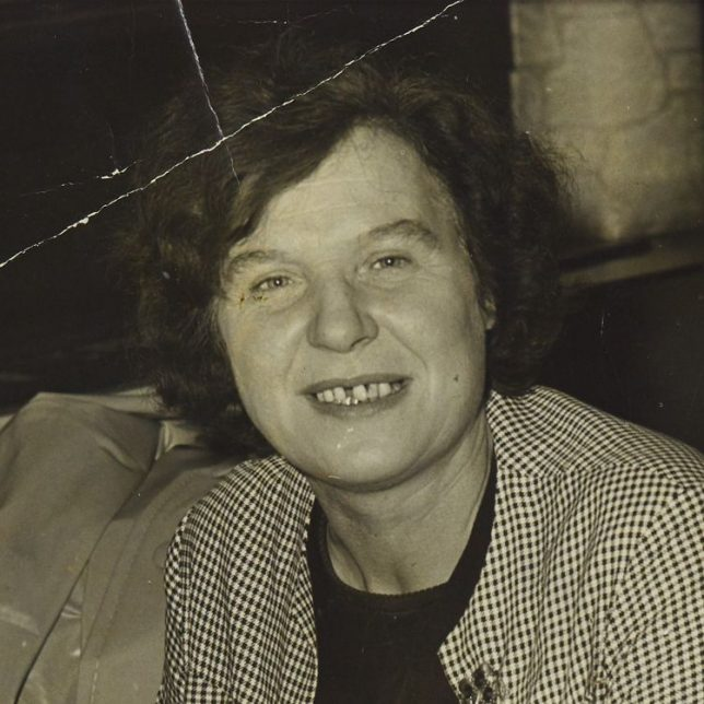 A black and white image of a woman looking at the camera. She has short hair and is smiling.