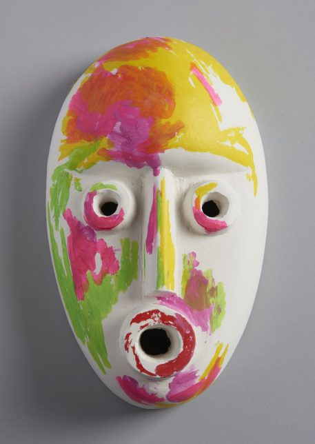 Mask (Yellow), 2018, by Ruth Barker - a stylised white ceramic mask painted abstractly with shades of yellow, pink and green