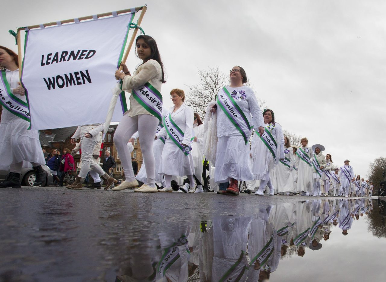 Women dressed in white with purple and green sashes process down a road.