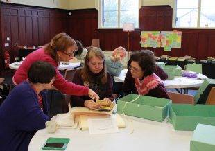 In the GWL main event space, some of the community curators look at small items from the collection.