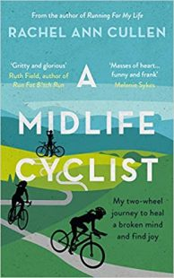 Cover of a Midlife Cyclist. The cover image is a drawing of fresh, green hills and a nice blue sky. There is a long pathway winding through the hills and there are silhouettes of three cyclists at different parts of the trail. The one farthest back is standing stationary next to her bike, drinking some water. The other two are riding their bikes further down the path.