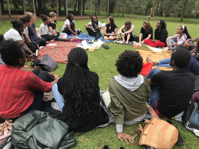 Image taken by Adele on her Clore Leadership Fellowship showing a group of women from Book Bunk and GWL sitting around in a circle on the grass listening to one woman, Wanjiru Koinange, as she talks.