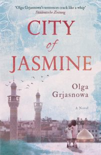 Cover of the City of Jasmine book. The background is a washed out light blue and pink colour with a water-coloured effect. In the bottom left corner of the book two children stand on a rooftop, the taller of the two has his arm around the smaller one. Their heads are pressed together. They are looking out at the city before them.