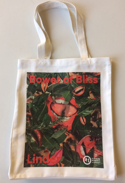 A white tote bag with a print on one side. The print has leaves and cut-out images of lips arranged amongst them. It says 'Bower of Bliss' at the top and 'Linder' at the bottom.