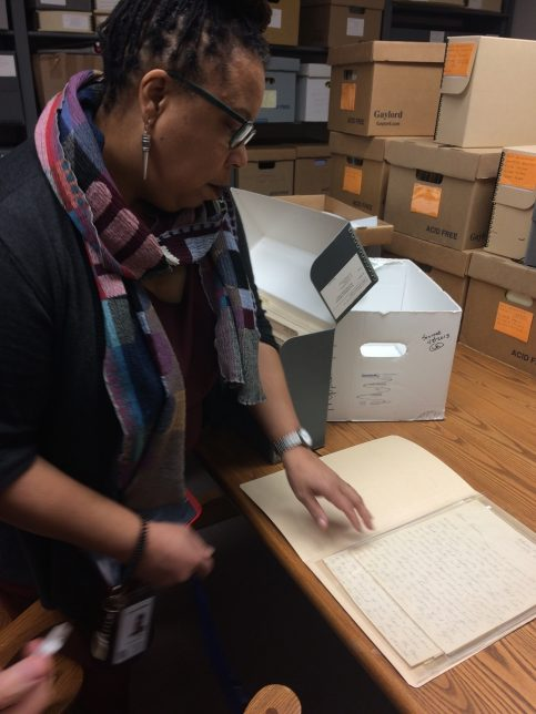 Image taken by Adele on her Clore Leadership Fellowship shows a woman, Lyonora Williams looking at a handwritten letter within an archive, surrounded by archival boxes.