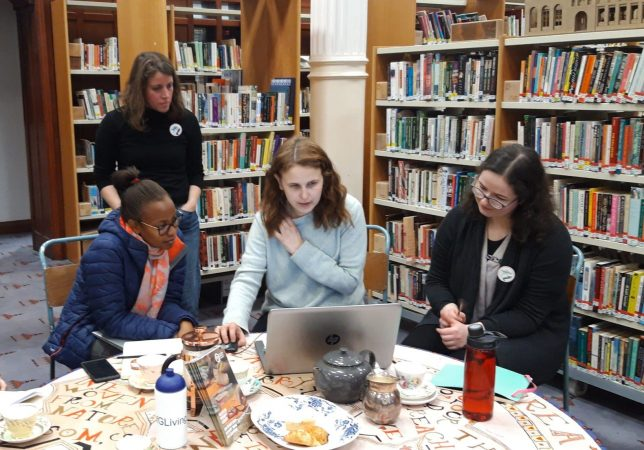 Four women working around a laptop at a round table filled with tea cups, buns and GWL programmes, with stacks of bookshelves behind.
