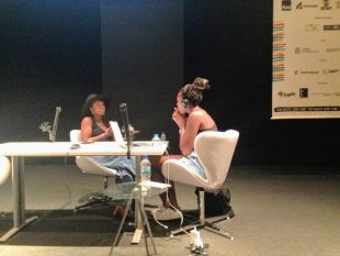 Tomiwa Folorunso with Funmilola Fagbamila - they are sitting at table with microphones, intent in conversation