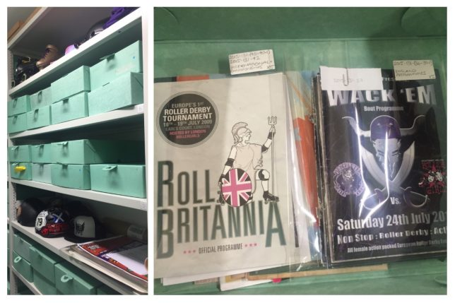 On the left, a a bay of shelves filled with green boxes and roller derby material, including helmets. On the right, a box filled with roller derby bout programmes; the top two are titled Roll Britannia and Wack 'Em.