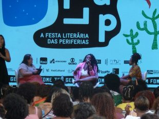 Flávia Oliveira and Roberta Estrela D'Alva, Akua Naru and Preta Rara interviewed by Jéssica Balbino - they are sitting on a low stage with the FLUP festival logo projected behind them
