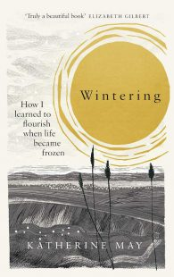 The cover of Wintering by Katherine May. Monochromatic artwork of a field with a river and mountain range in the distance. A dull ochre colored sun takes up most of the sky.