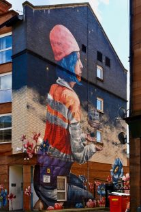 Mural on gable end of a block of flats, showing a woman with blue hair, a pink hat and an orange high vis vest, and flowers growing around her.