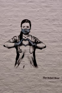 Mural depicting a doctor or nurse wearing a face mask and holding her hands together to make the shape of a heart