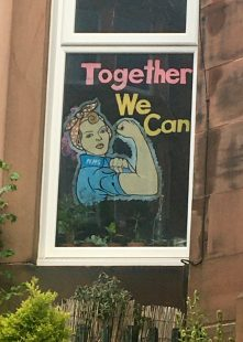 "Paper cut out stuck to the inside of a window of the words ""Together we can"" and a drawing of Rosie the Riveter, a woman in blue overalls and a red head scarf flexing her arm muscle (from the 1940's poster)"