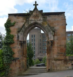 Sandstone archway with a cross on the top, with ivy growing up on side.