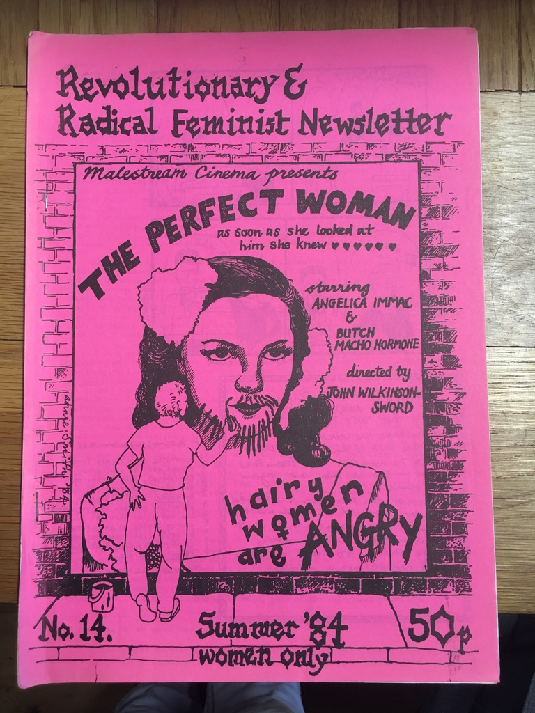 A bright pink cover of the feminist newsletter with black writing and a black drawing of a movie poster with a woman graffitiing a beard onto the movie star on the poster. She has also scribbled, 'hairy woman are angry' in the corner of the poster.