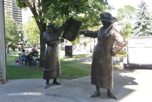 """Bronze statue of two women in early 20th century dress holding up a newspaper which reads: """"Women are Persons"""""""