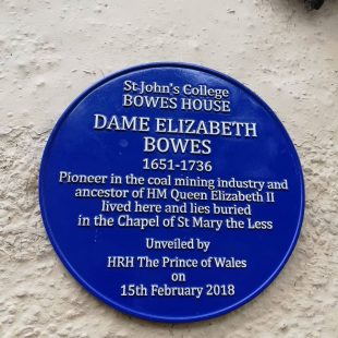 """Circular blue plaque with white writing commemorating Dame Elizabeth Bowes, 1651-1736. It says: """"Pioneer in the coal mining industry and ancestor of HM Queen Elizabeth II lived here and lies buried in the Chapel of St Mary the Less. Unveiled by HRH The Prince of Wales on 15th February 2018"""""""
