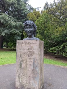"""Bust of a woman sitting on a pedestal of stone engraved with the name """"Sheila McKechnie"""". The monument appears to be in a park with tress in the background."""