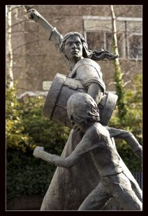 Statue of two people marching: a determined looking young woman holding a drum which she is beating with a clenched fist, and a child walking alongside her and looking up to her, whose face we cannot see