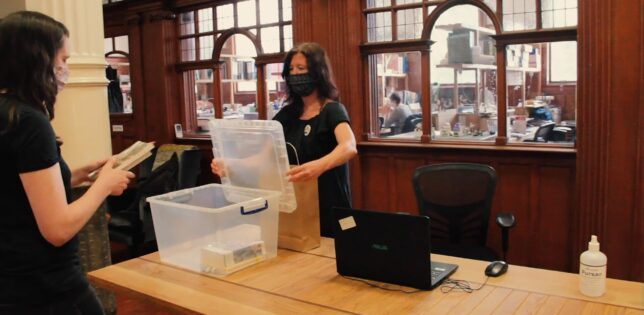 Screenshot from GWL Covid-19 Safety Procedures video - our librarian opens a plastic box for a visitor to place a returned book into. They are both wearing facemasks.