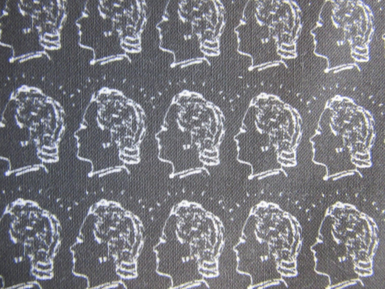 Patterned fabric design for our GWL facemasks, in white on black with the 'Women in Profile' logo from GWL's precursor, a woman's head with short lines radiating outwards.