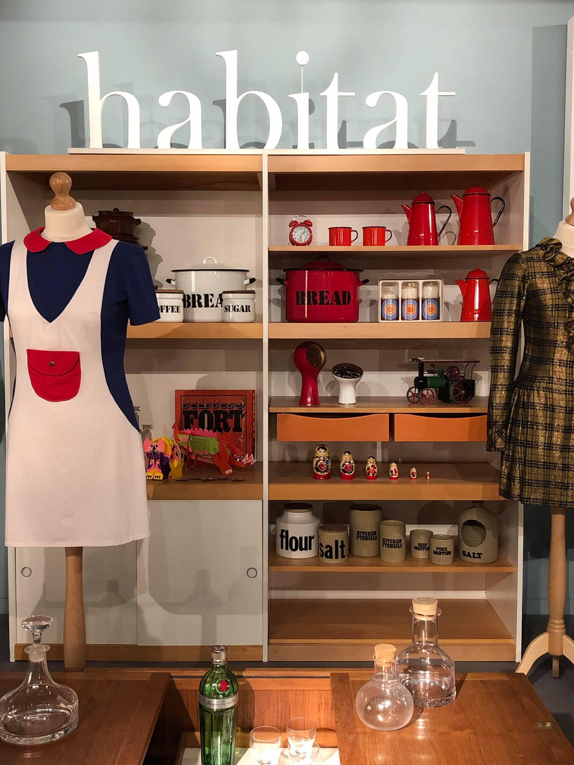 This photo shows a pale blue background wall in front of which a large shelving unit stands. On top of the uni is a large white 'habitat' sign and the shelves hold several household habitat designs including bread bins, alarm clocks, and coffee pots. In front of the shelves are two mannequins, one wearing a blue red and white pinafore style minidress, and one wearing a shiny gold and brown checked lame party dress.