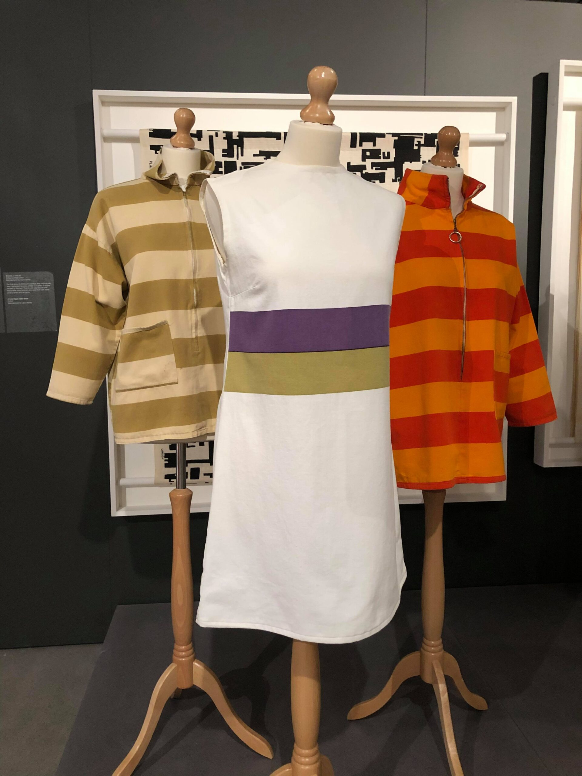 This photo shows a black background wall, with a large white square frame hanging on it. In the frame is a sample of a black and white patterned fabric. In the foreground are three mannequins. Two of them wear striped canvas gardening smocks, on the left is a beige and green one, on the right a bright orange and red. The front mannequin wears a white basic sleeveless minidress with two thick stripes across the waist, one in purple and one in green.