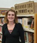 Mattie in front of a bookshelf