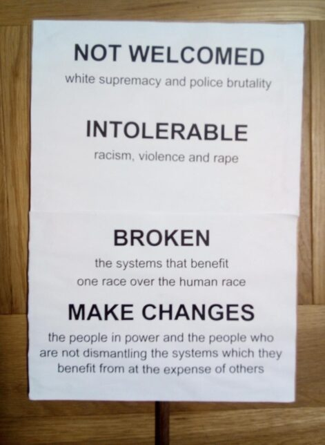 Black Lives Matter protest placard which reads in plain black text on a white background: NOT WELCOMED white supremacy and police brutality / INTOLERABLE racism, violence and rape / BROKEN the systems that benefit one race over the human race / MAKE CHANGES the people in power and the people who are not dismantling the systems which they benefit from at the expense of others