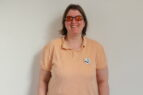 Doreen stands against a white wall. Doreen wears a peach polo shirt. Her hair is in a bob style and she wears glasses with orange tinted lenses.