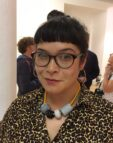 Naomi is wearing glasses, a leoprad print shirt and large beads around her neck. Naomi has dark hair tied up with a fringe