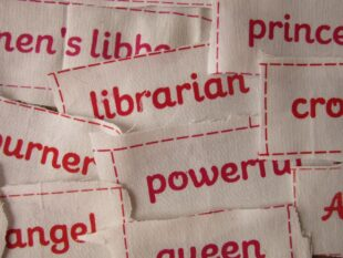 Detail of a pile of white cloth scraps that have different derogatory everyday words for women and feminists printed on them in red.
