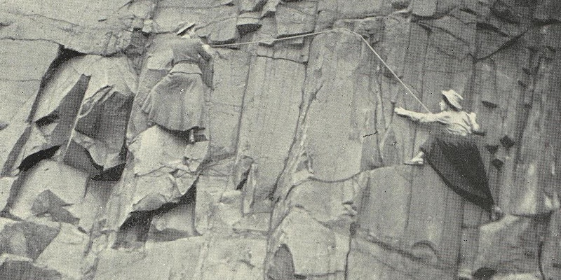 Two women wearing skirts are scaling a cliff in a black and white photo.