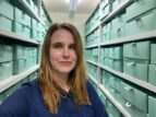 Archivist Nicola Maksymuik, photographed in the GWL Archive stores - there are white shelves full of pale green archive boxes on either side of a corridor behind her