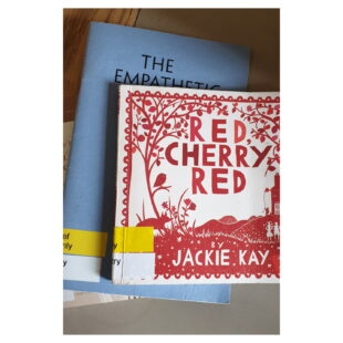 Jackie Kay's Red Cherry Red sits atop a pile of books