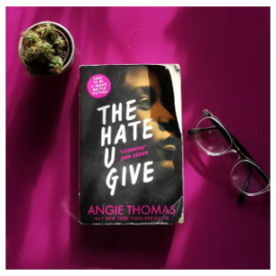 """a small potted cactus sits at the top on the image. at the centre is the book """"THE HATE U GIVE"""" beside which to the right is a pair of glasses"""