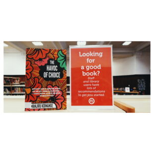 """The Havoc of Choice sits on a shelf beside a red sign which reads """"Looking for a good book?"""""""